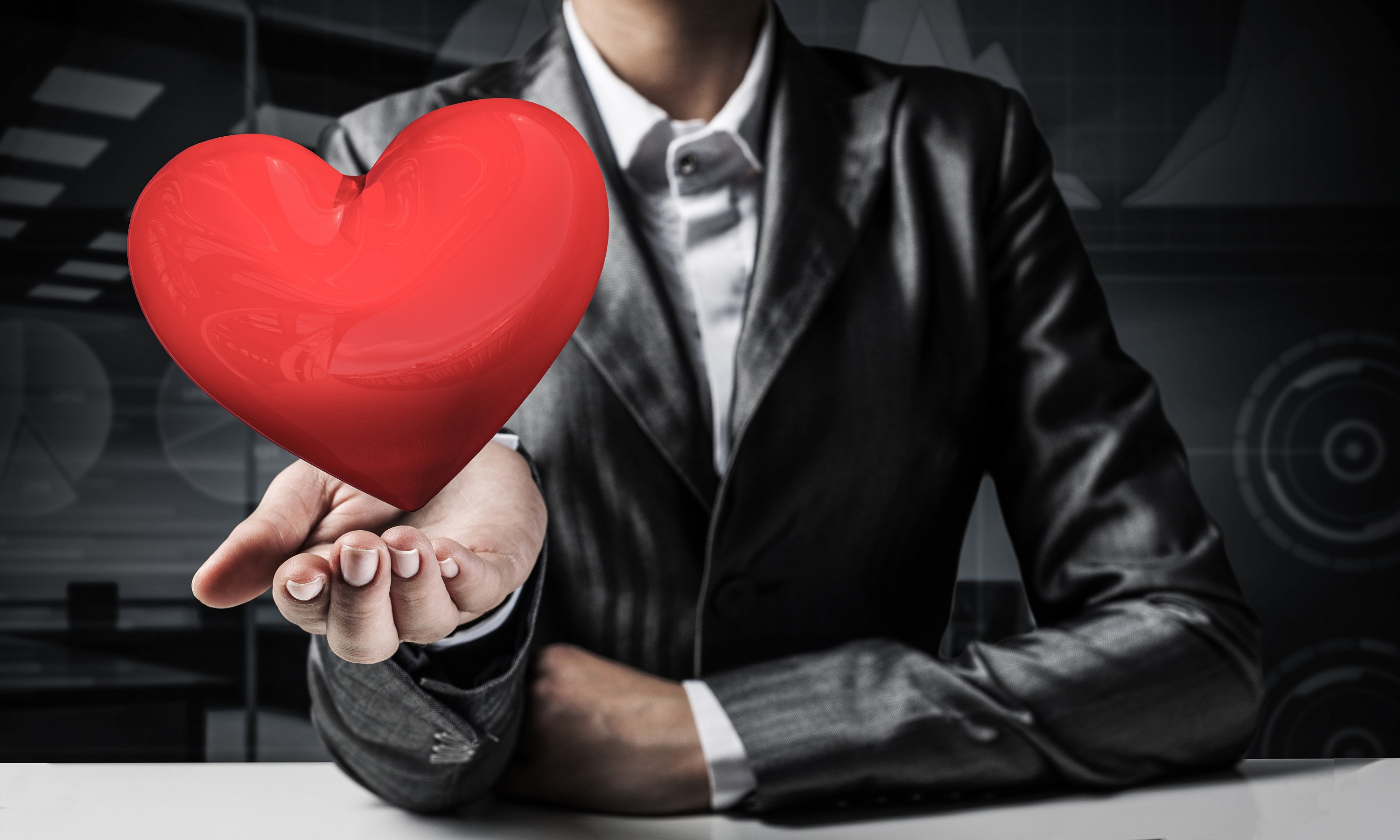 Cropped image of businessman in suit presenting big red heart his hand with dark office view on background. 3D rendering.