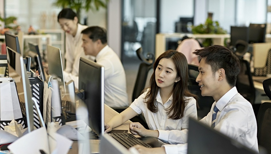 Chinese male and female business associates in their 20s sharing office computer and working on research project together.