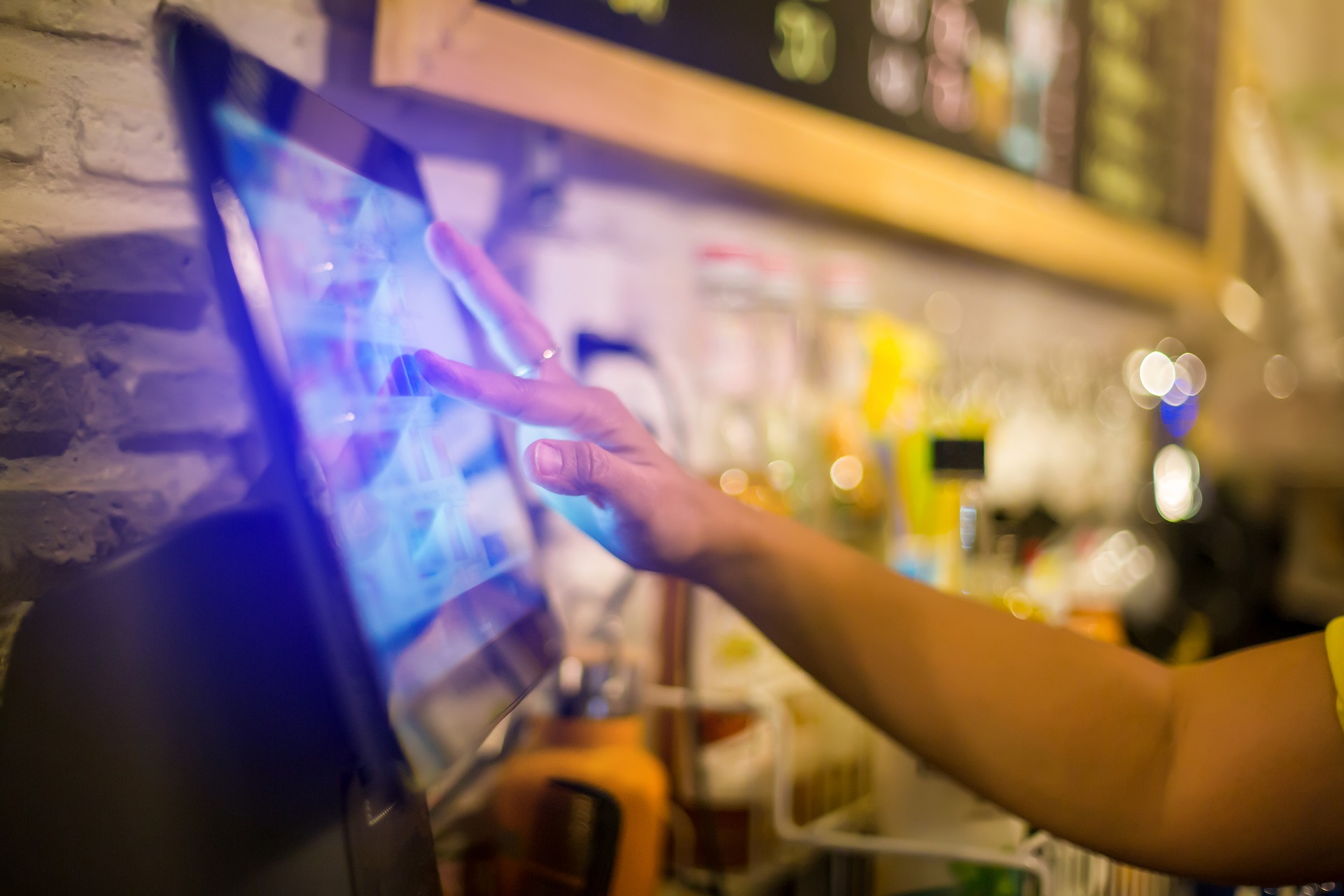 Blurry picture of cashier is making order on touch screen of computer in cafe or store. Barista is using the screen to receive orders from customers who are pointing to order coffee.